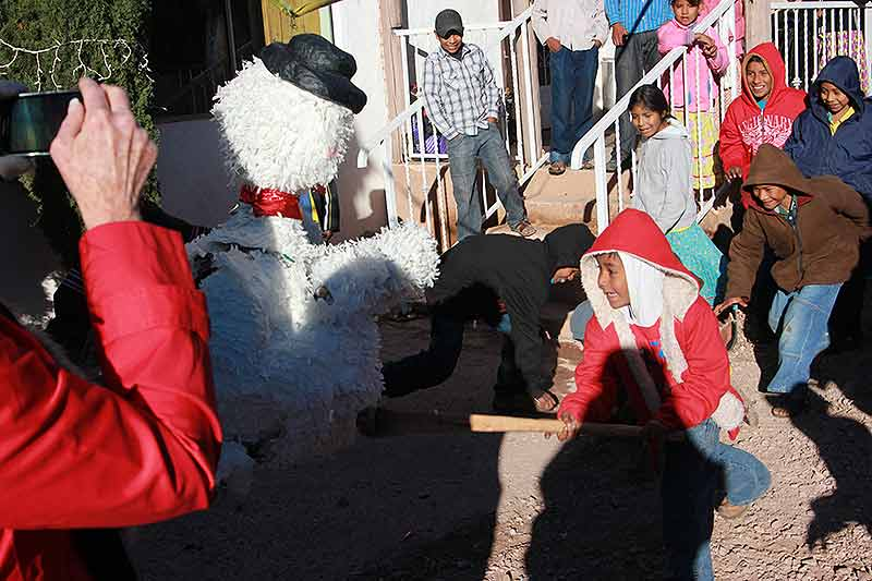 Raramuri boy whacking at the Piñata and spilling out candy. Copper Canyon, Mexico
