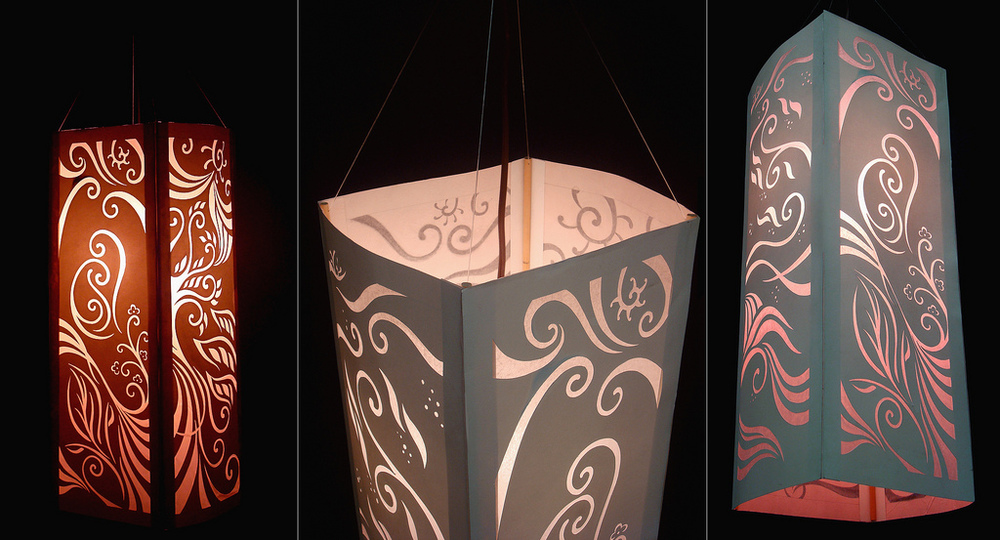 paper lantern with original designs cut out using an xacto knife on each panel