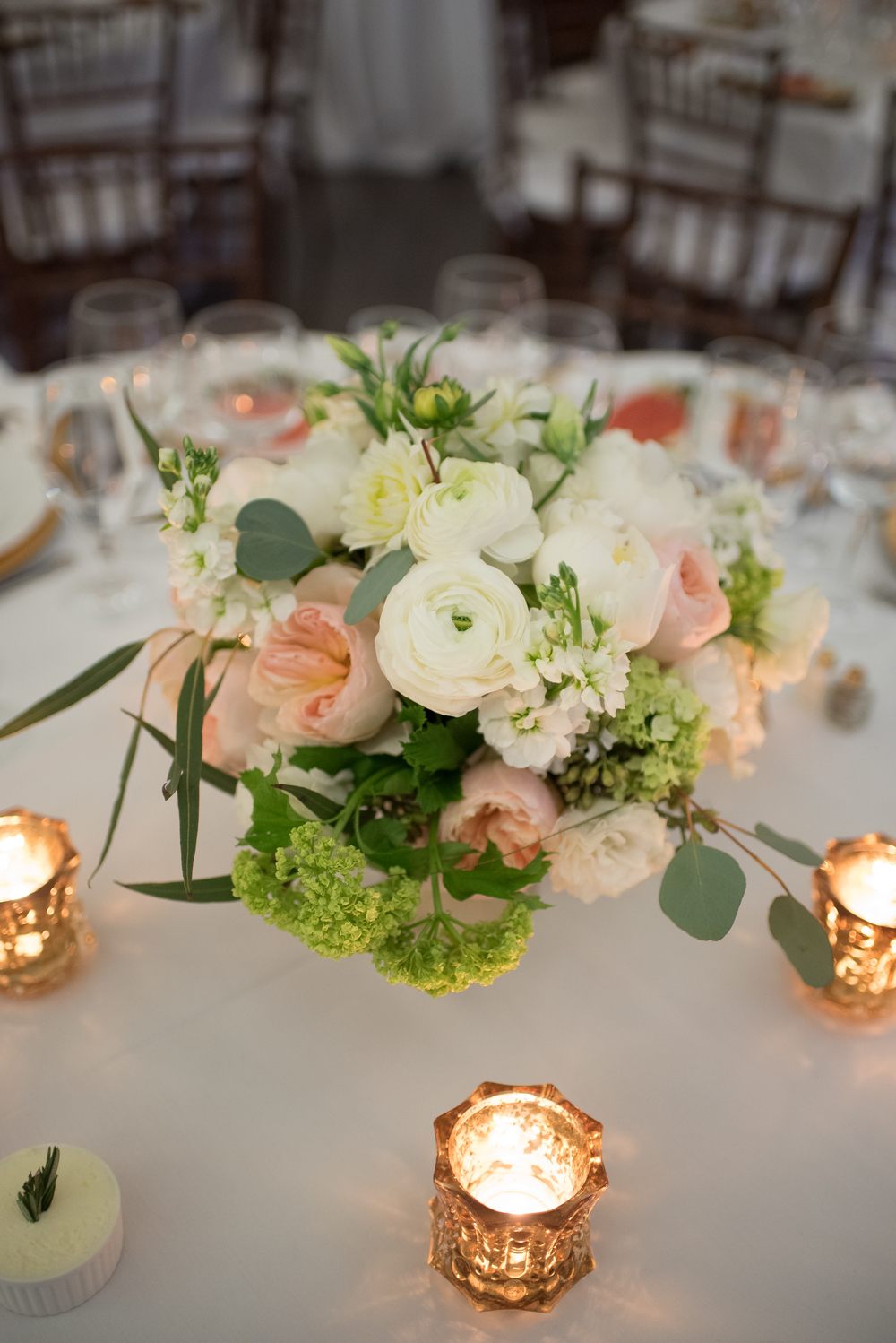 With the lower arrangements, we incorporated more green and peach aspects surrounded by beautiful candlelight.