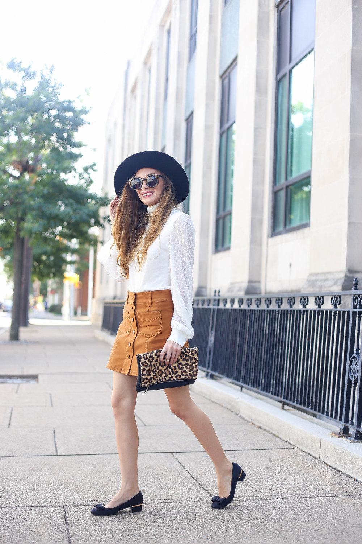 White Sweater, tan skirt, black heels, leopard clutch.