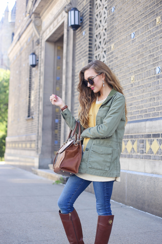 Mustard Sweater. Skinny Jeans. Karen Walker Sunglasses. Tan Riding Boots. Cognac Bag. Olive Green Jacket.