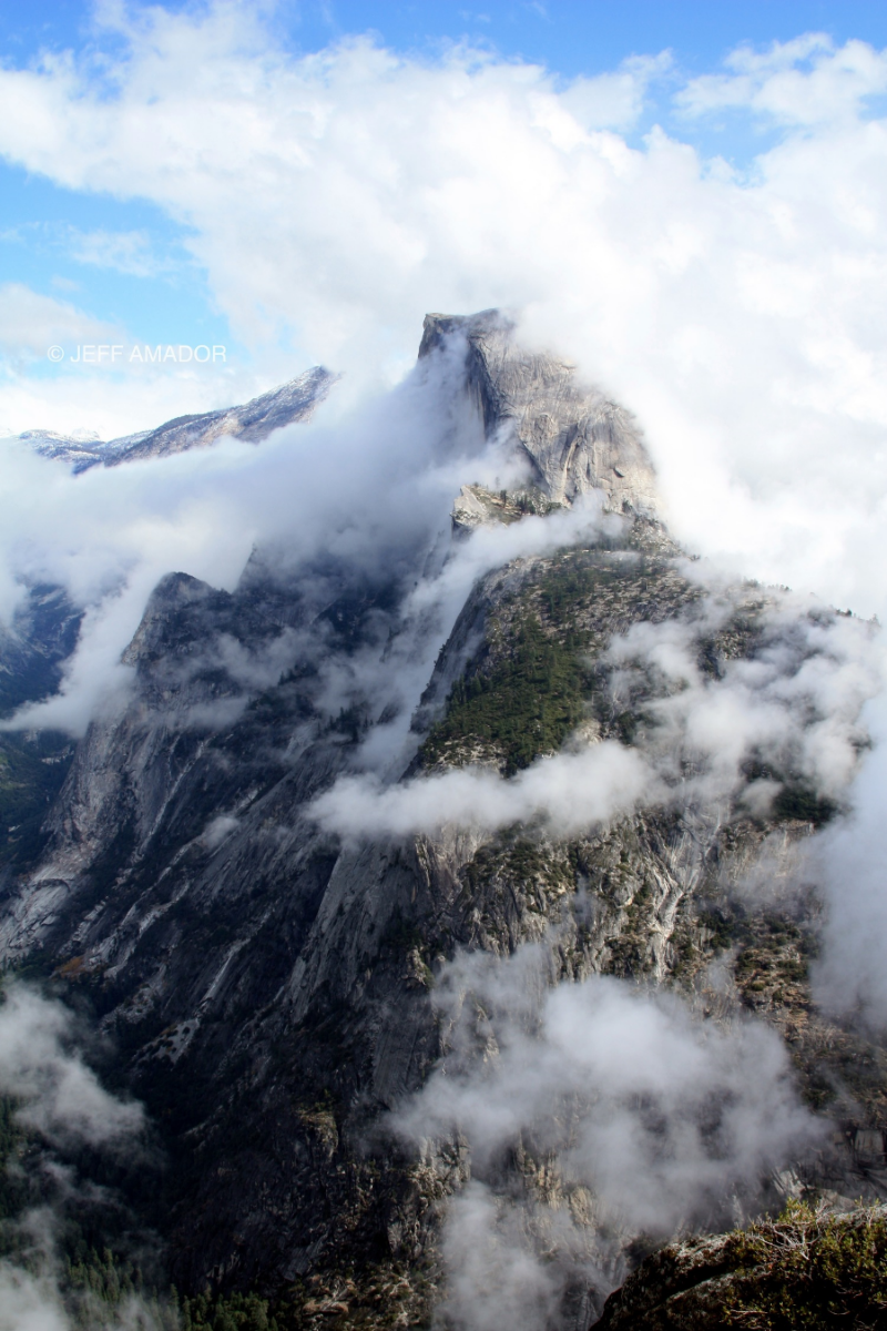 A break in the clouds offers a unique view of Half Dome battling against the clouds