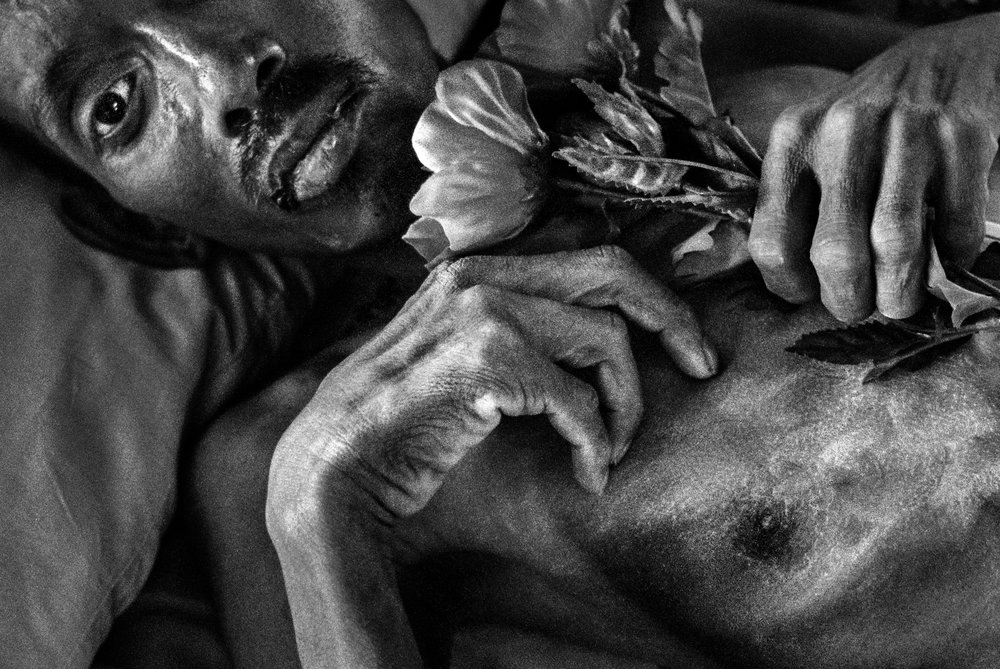 This image was one of 75 images selected by the Pictures of the Year International for their 75th Anniversary Exhibition.  THAILAND, 1998. Saong (38) lies in an AIDS hospice, covered in a light dusting of powder and holding a plastic flower that he described as beautiful. Since the Asian economic crisis in the late 1990s, the Thai government's funding for AIDS care was cut, and this hospice raised money by selling plastic flowers for visitors to give to the patients. After visitors left the flowers were collected from the patients to be re-sold again to the next group. Saong said he didn't mind the recycling of the flowers and handing it back over. Instead, it was the gesture of giving the flower that was beautiful to him. Th photograph, made on a trip for the The Washington Post was recognized at the time with a World Press Photo award as well.