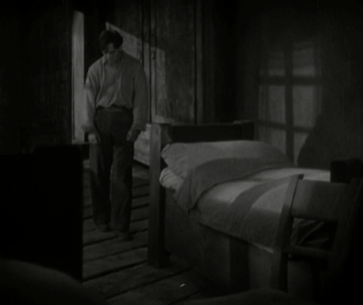 Image 3. The man moves very slowly into the room, his shoulders slumped, he looks defeated. As he enters the light and notices the empty bed of his wife, who he thinks is dead.