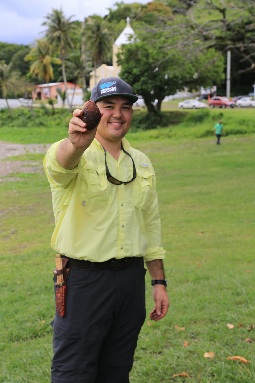 Dr. Austin Shelton holding a 'seed slingstone' used as a watershed restoration tool to reforest eroding hillsides and reduce sedimentation on downstream coral reefs