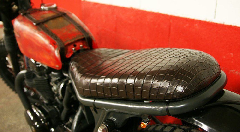 - bespoke seat designed to match the shortened subframe;  - bespoke seat cover  100% hand made  by  RM Williams  in crocodile skin.