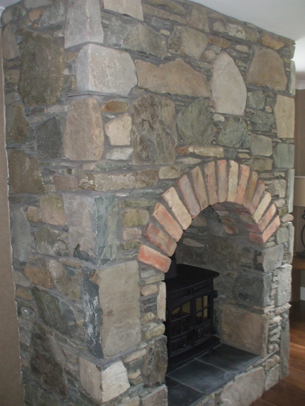 Fireplace built with field stone and red Belfast brick