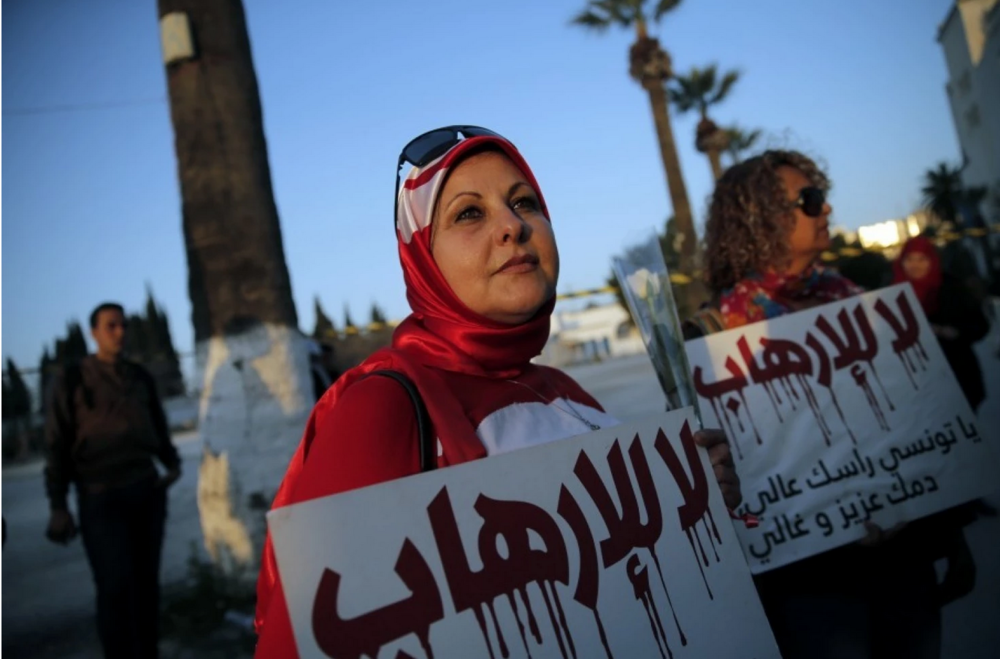 "A woman holds a placard reading: ""No to Terrorism"" as she demonstrates in front of the National Bardo Museum a day after gunmen attacked the museum and killed scores of people in Tunis, Tunisia, Thursday, March 19, 2015."
