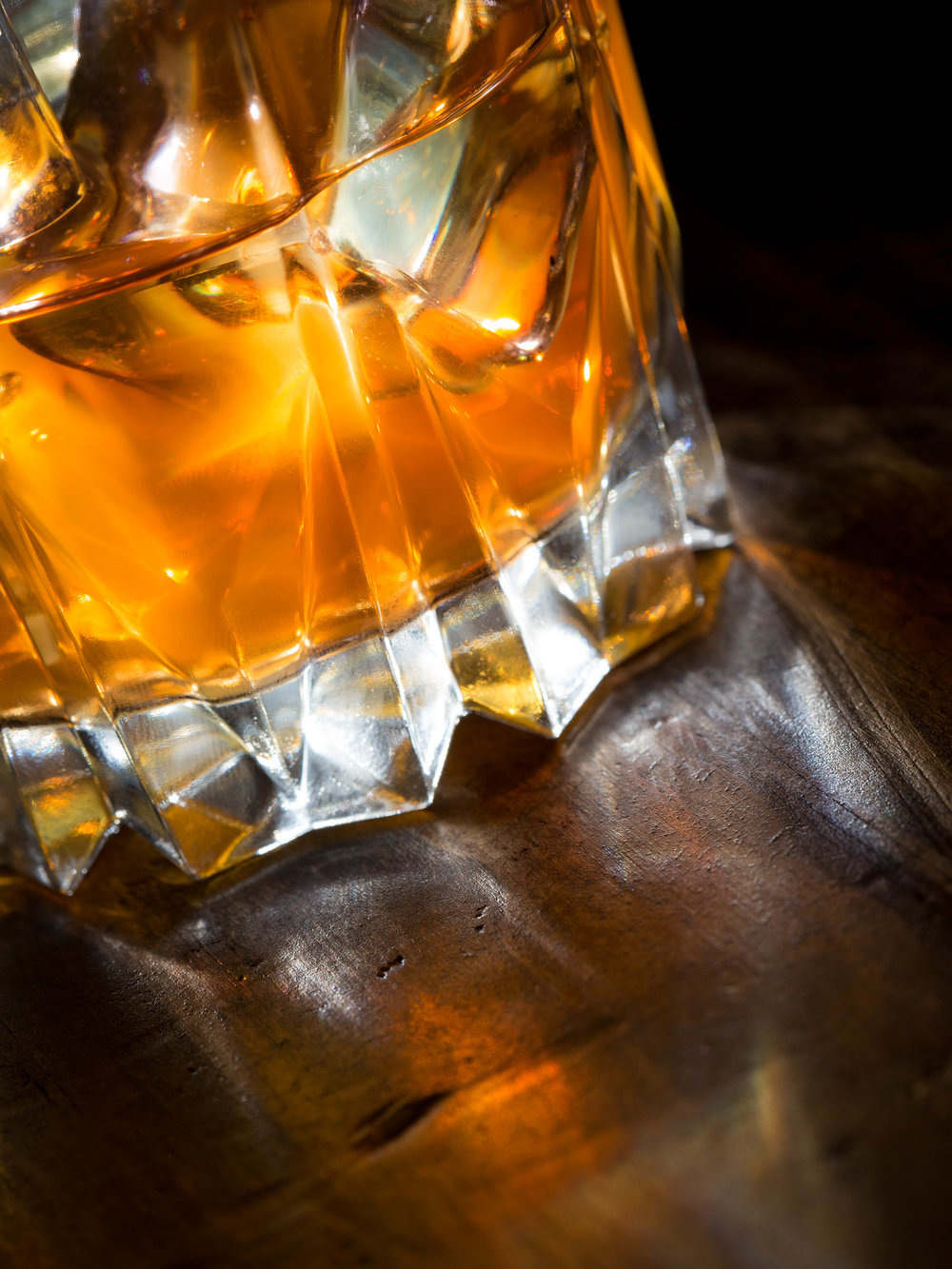 Close-up of whisky glass abstract compostion with light shining through glass