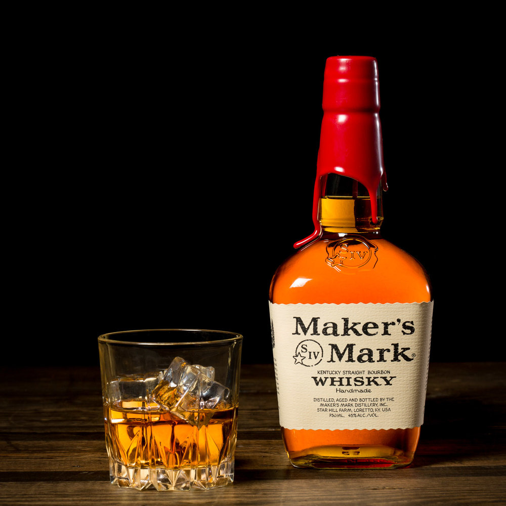 Makers Mark whisky advertisement bottle and glassware on wood table.