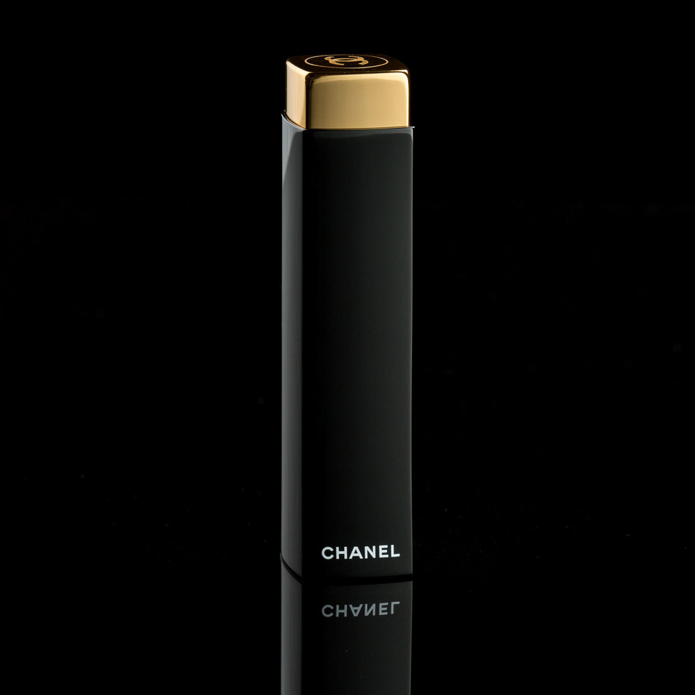 Simple and elegant image of a Chanel lipstick. The image showcases the photographer skill in lighting a black object on a black background. Highlights are controlled so that the lipstick separates from the background and the gold reflective cap has a pleasing gradated highlight. Shot in Los Angeles studio.