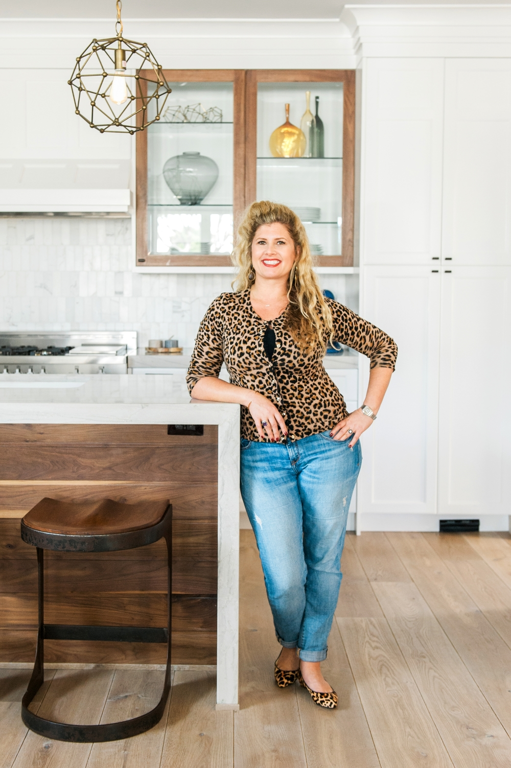 Valerie Saunders, Principal Designer at Sérendipité, poses in her client's newly designed kitchen  photography by: Melissa Brandman