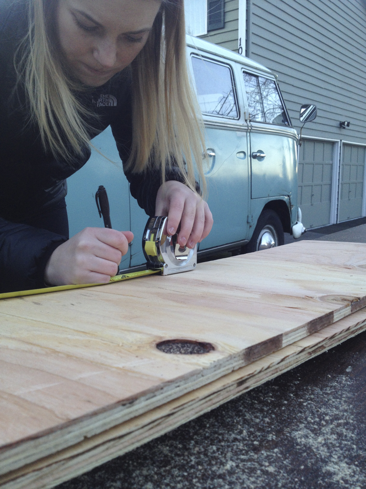 Danielle measuring the sub-floor sections. (That's Ben's bus in the background.)