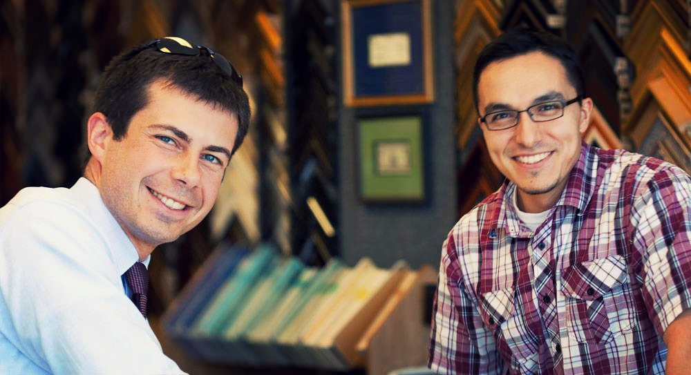 South Bend's mayor pete buttigieg (left) takes a photo with the owner of the frame factory, salvador moya (right).