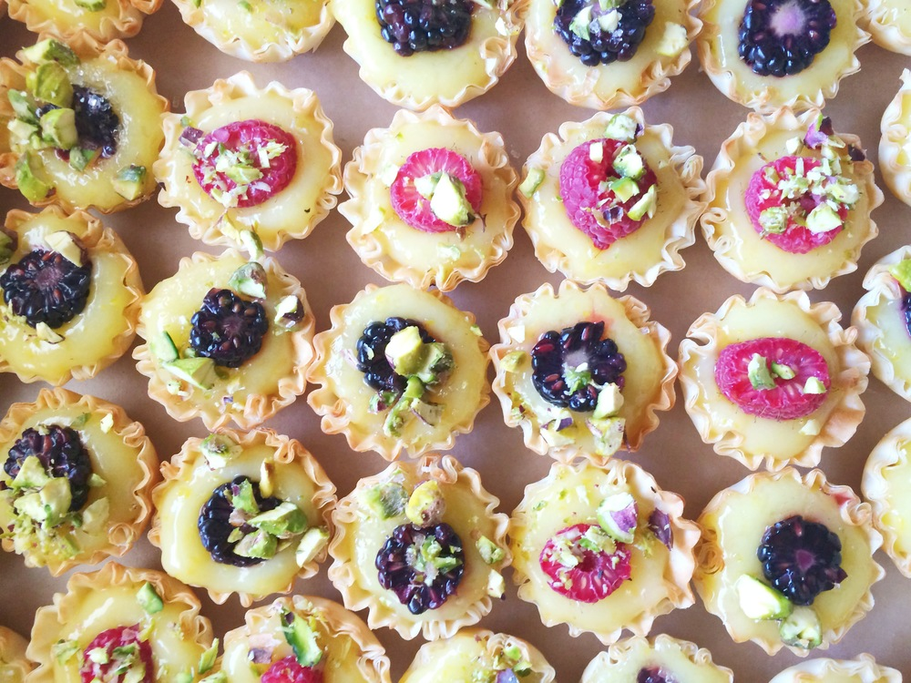 Miniature lemon tarts with berries and pistachios.