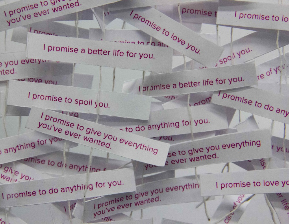 Multiple strings of promises hang inside the storefront windows, representing the false promises a pimp would say to his victim.