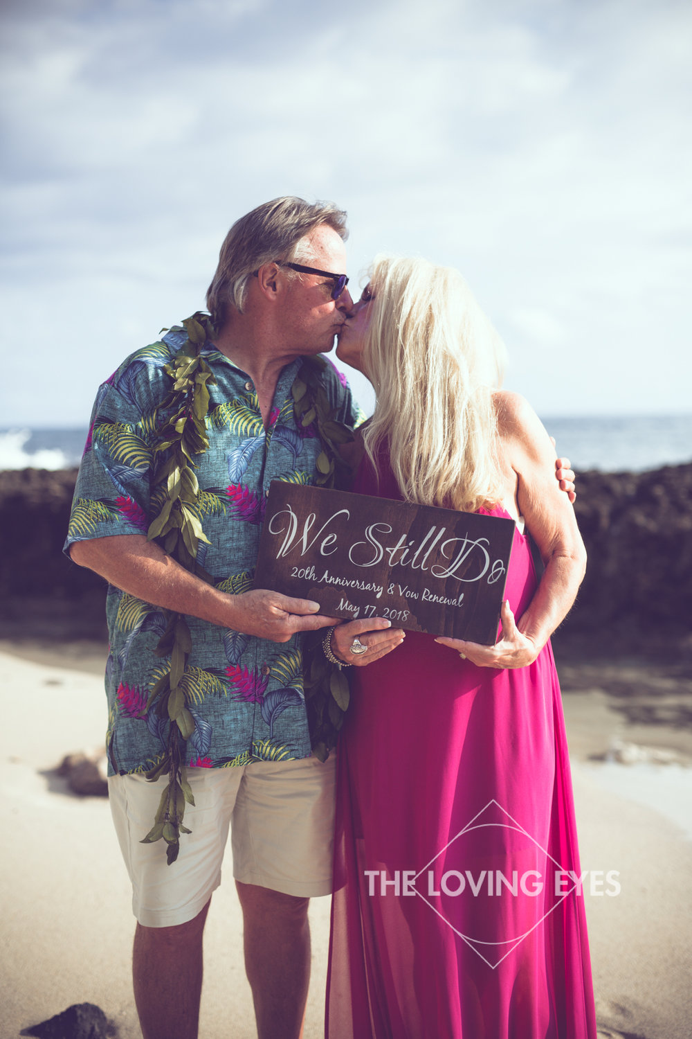 Couple holding up sign during vow renewal ceremony on the beach at Ko Olina Four Seasons Lagoon