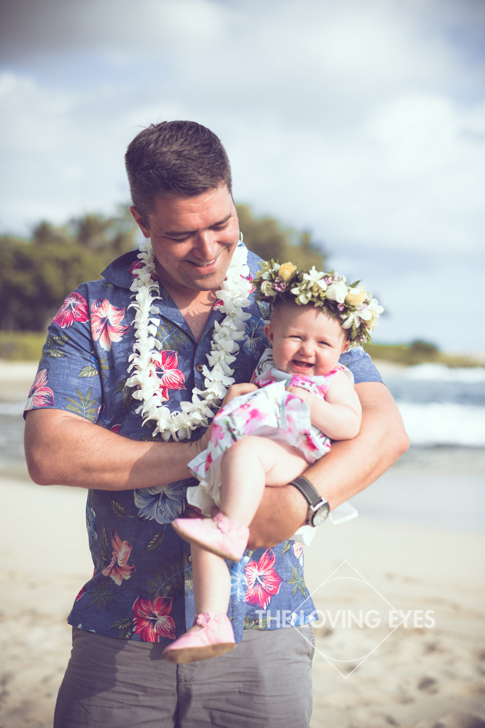 Father holding laughing baby on the beach at Ko Olina Four Seasons Lagoon