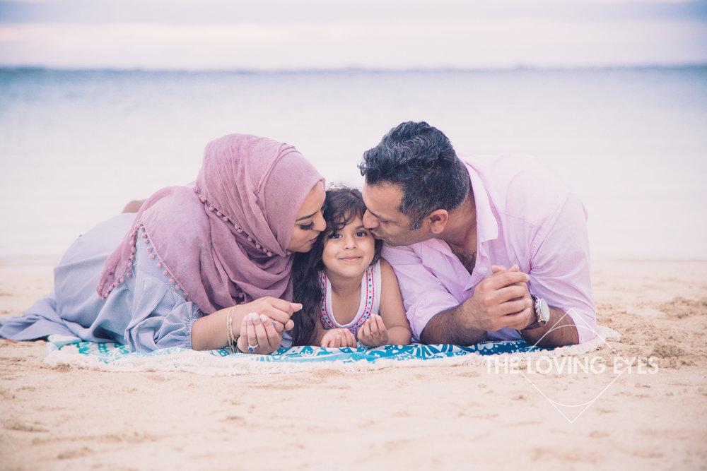 Family vacation photography kissing on the beach at Ala Moana Beach Park