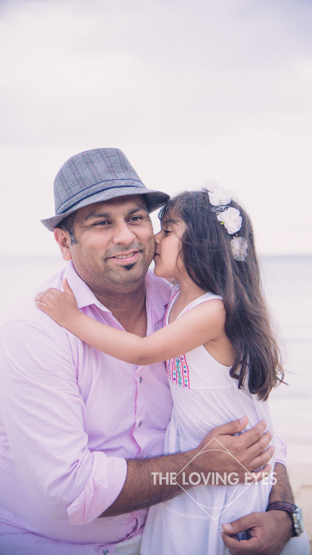 Daughter kissing father on the beach at Ala Moana Beach Park during Family vacation