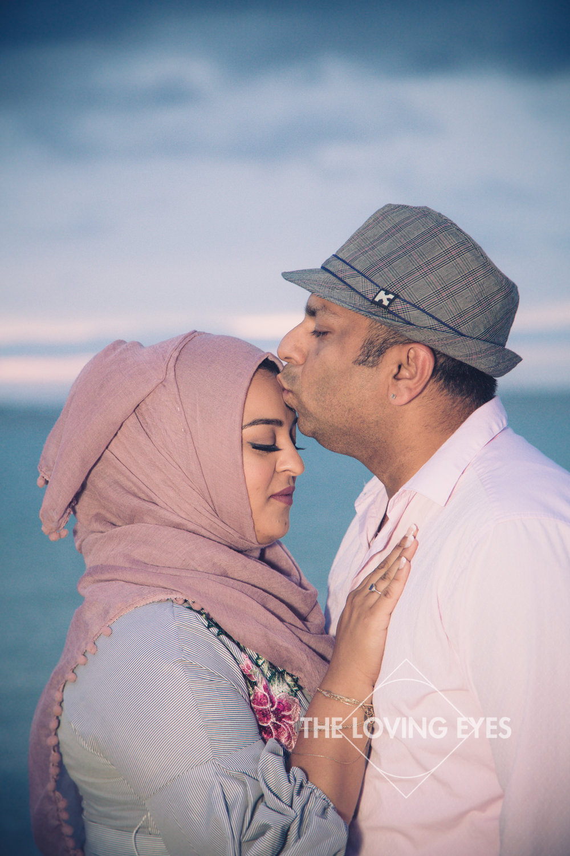 Couple kissing on the beach during sunset at Ala Moana Beach Park