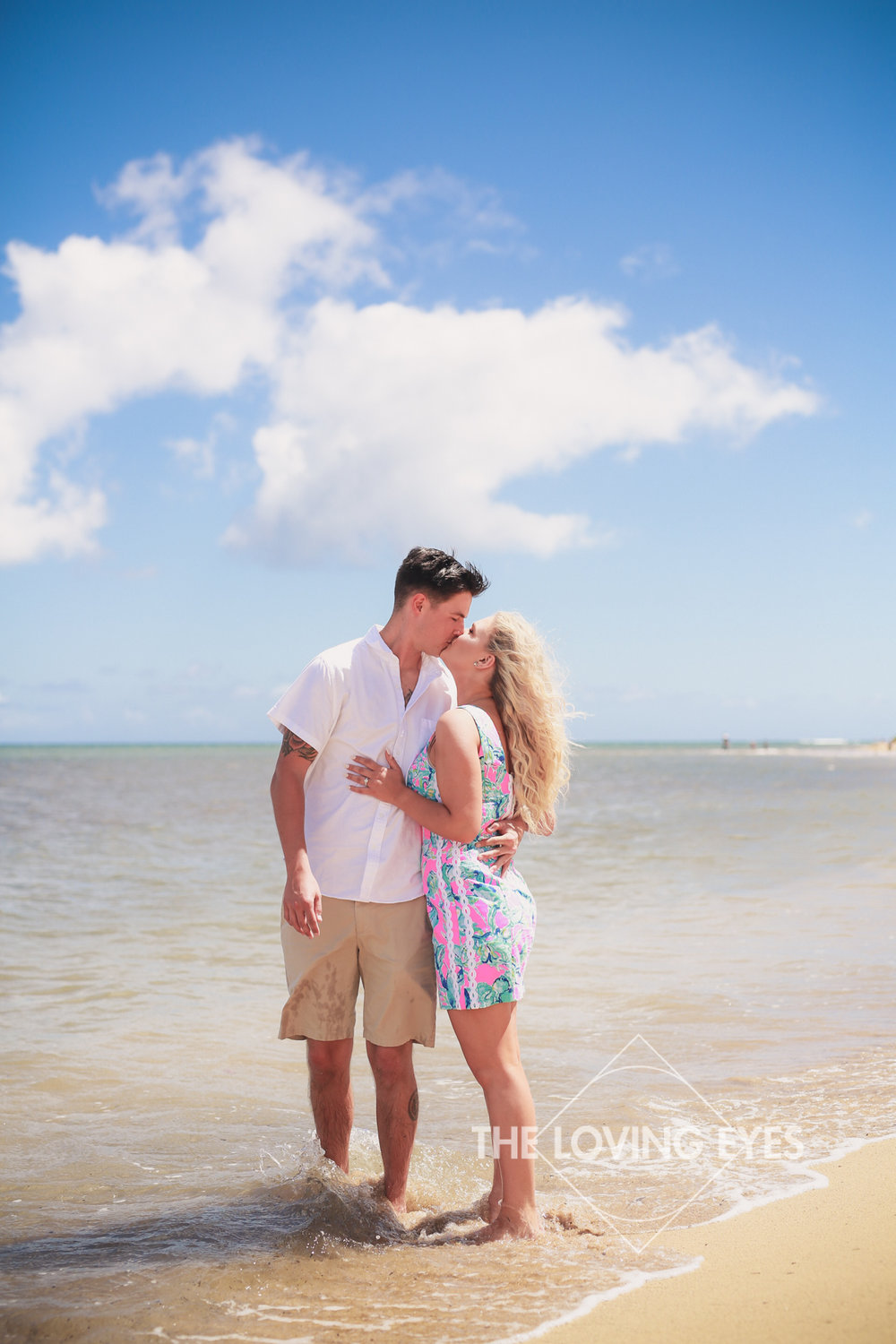 Kissing on the beach during engagement photo session at Waialae Beach Park