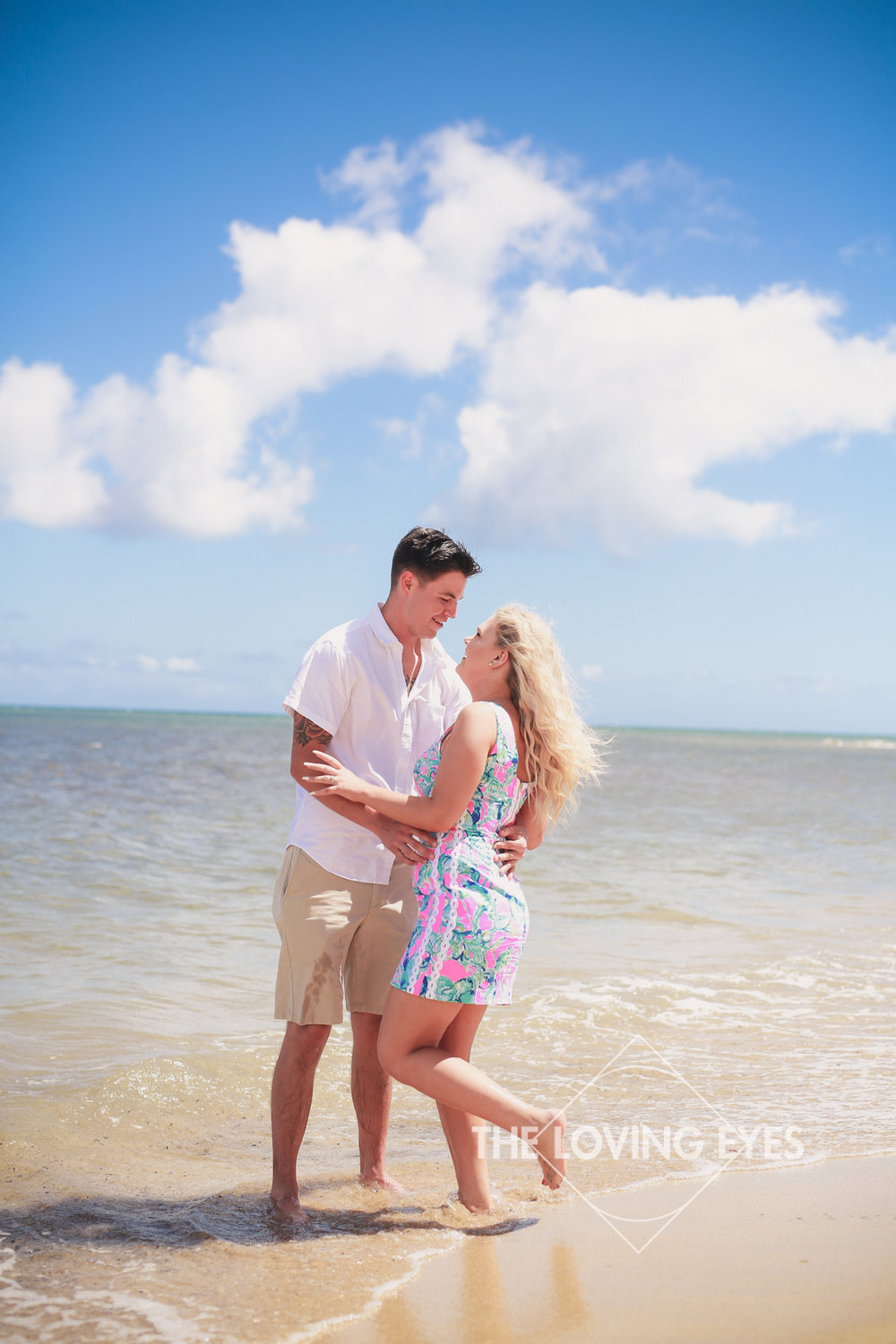 Couple holding each other on the beach during engagement photo session at Waialae Beach Park