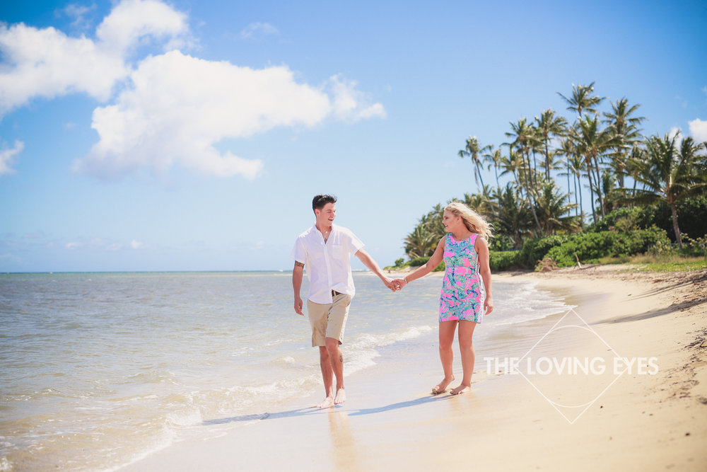 Walking hand in hand on the beach in Hawaii during engagement photo session at Waialae Beach Park