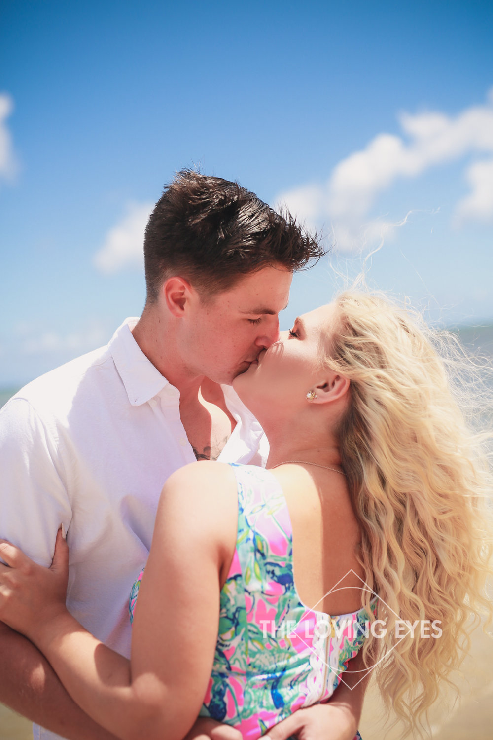 Kissing on the beach in Hawaii during engagement photo session at Waialae Beach Park