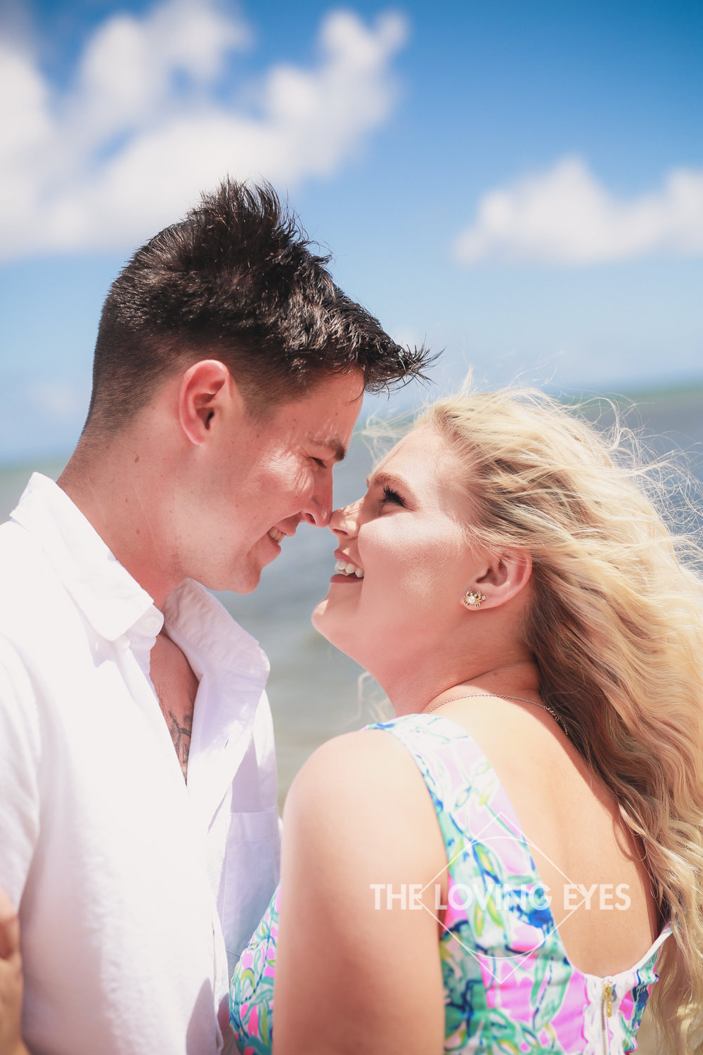 Couple holding each other on the beach in Hawaii during engagement photo session at Waialae Beach Park