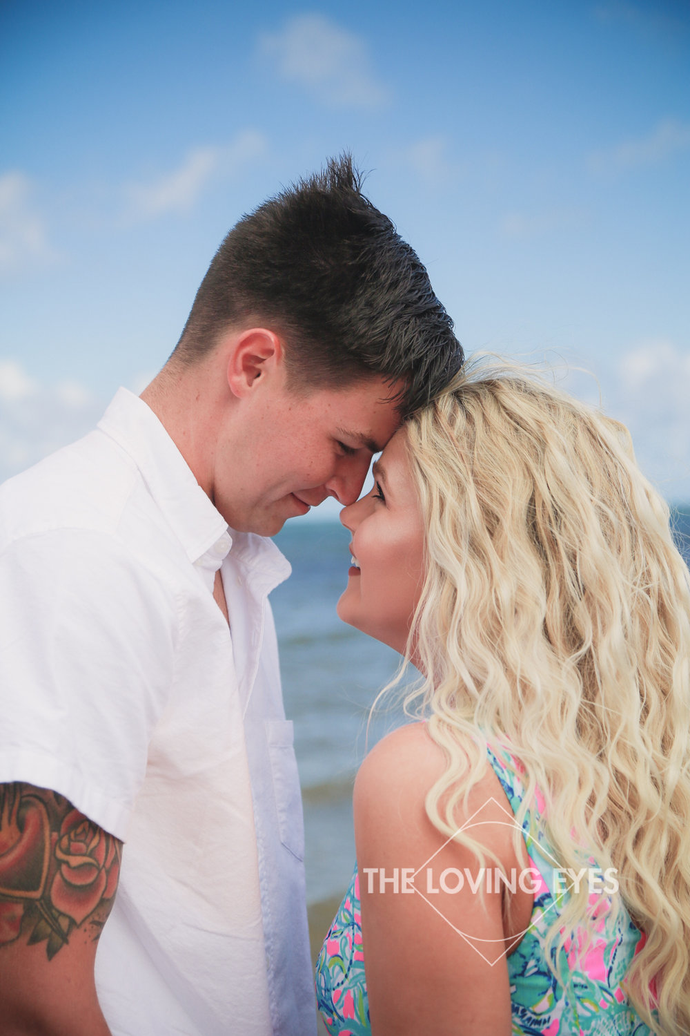 Staring into each other's eyes on the beach in Hawaii during engagement photo session at Waialae Beach Park