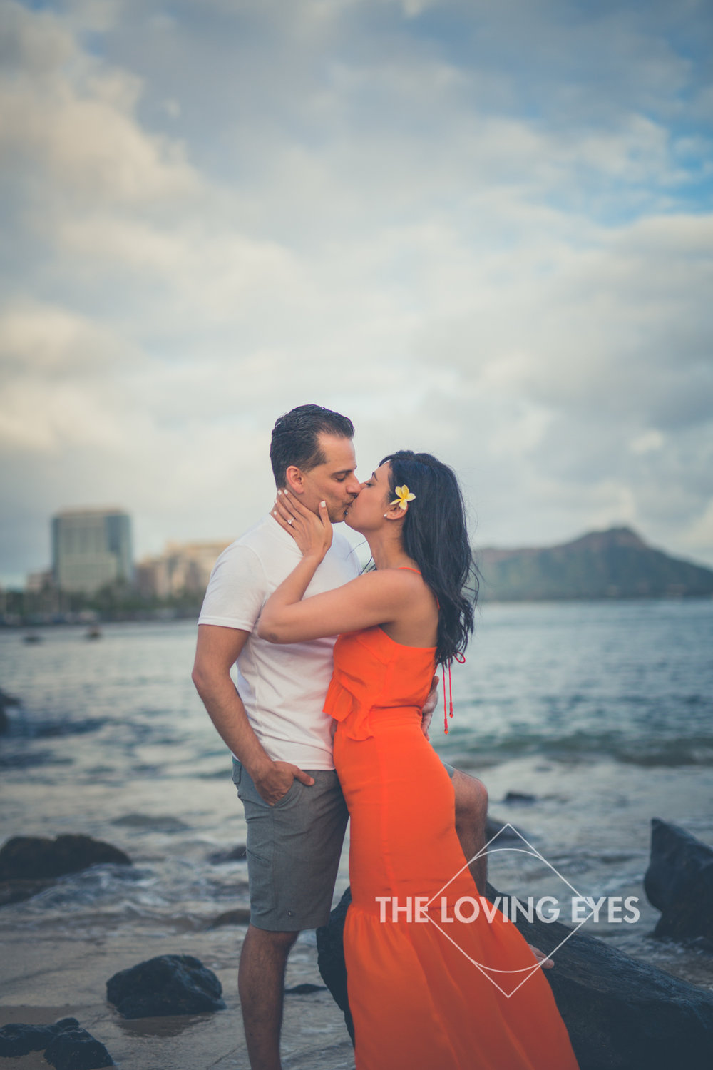 Couple kissing on the beach at Ala Moana Beach Park with Diamond Head in the background