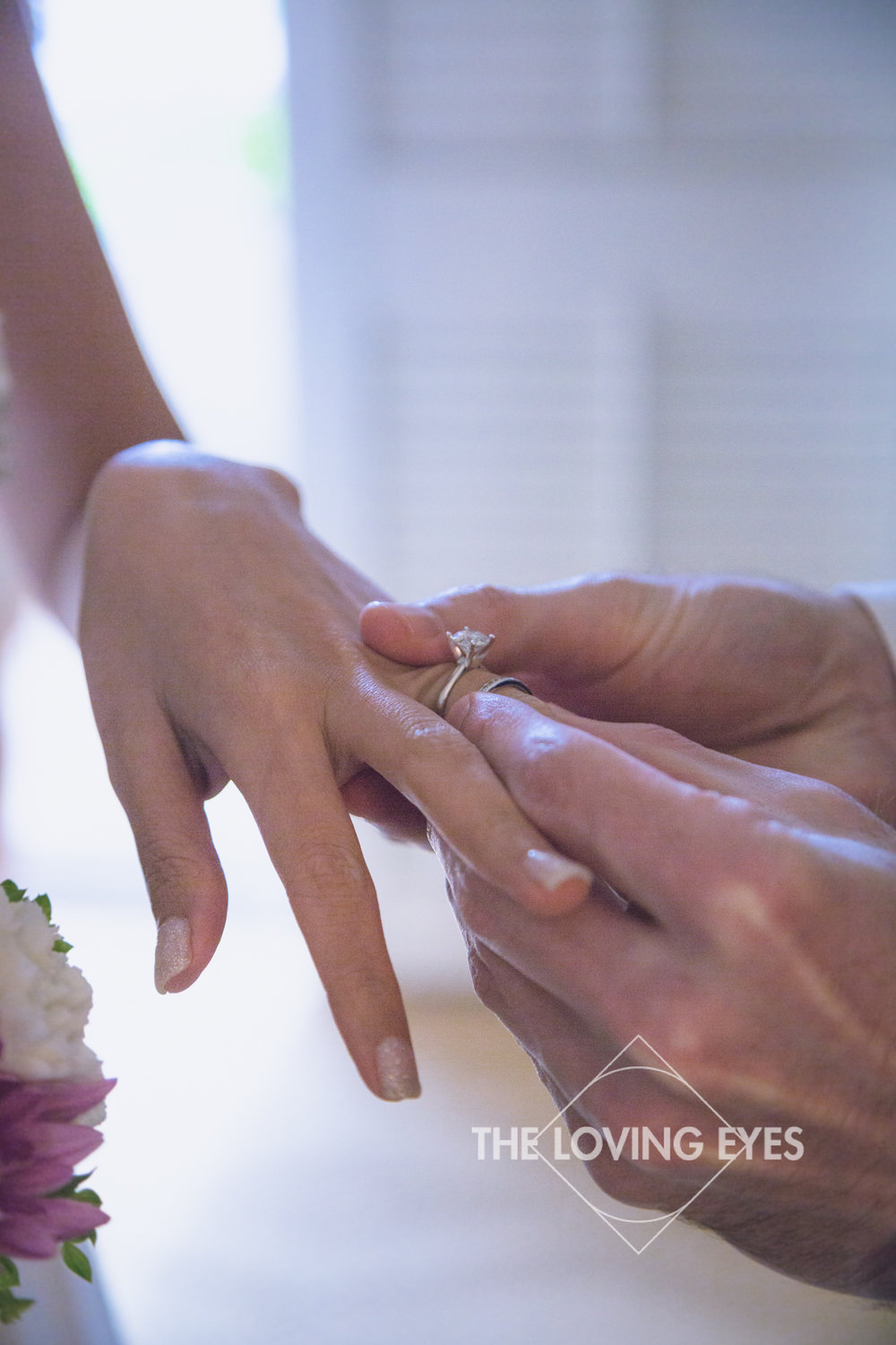 Groom placing wedding ring on his bride's finger at the Four Seasons Resort at Ko Olina