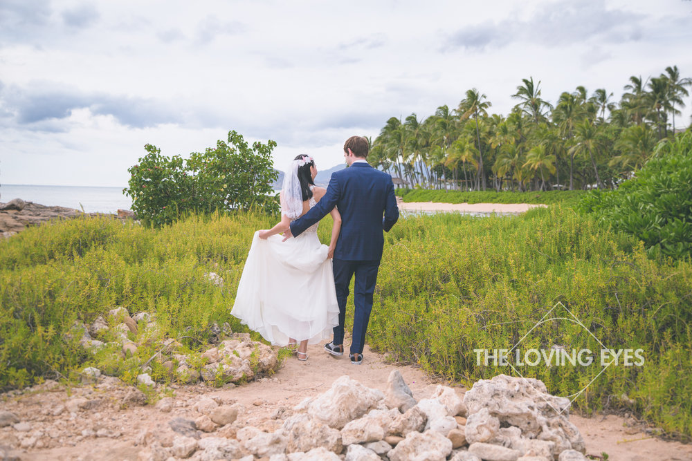 Bride and groom walking out to the lagoon near the Four Seasons Resort at Ko Olina before their wedding ceremony