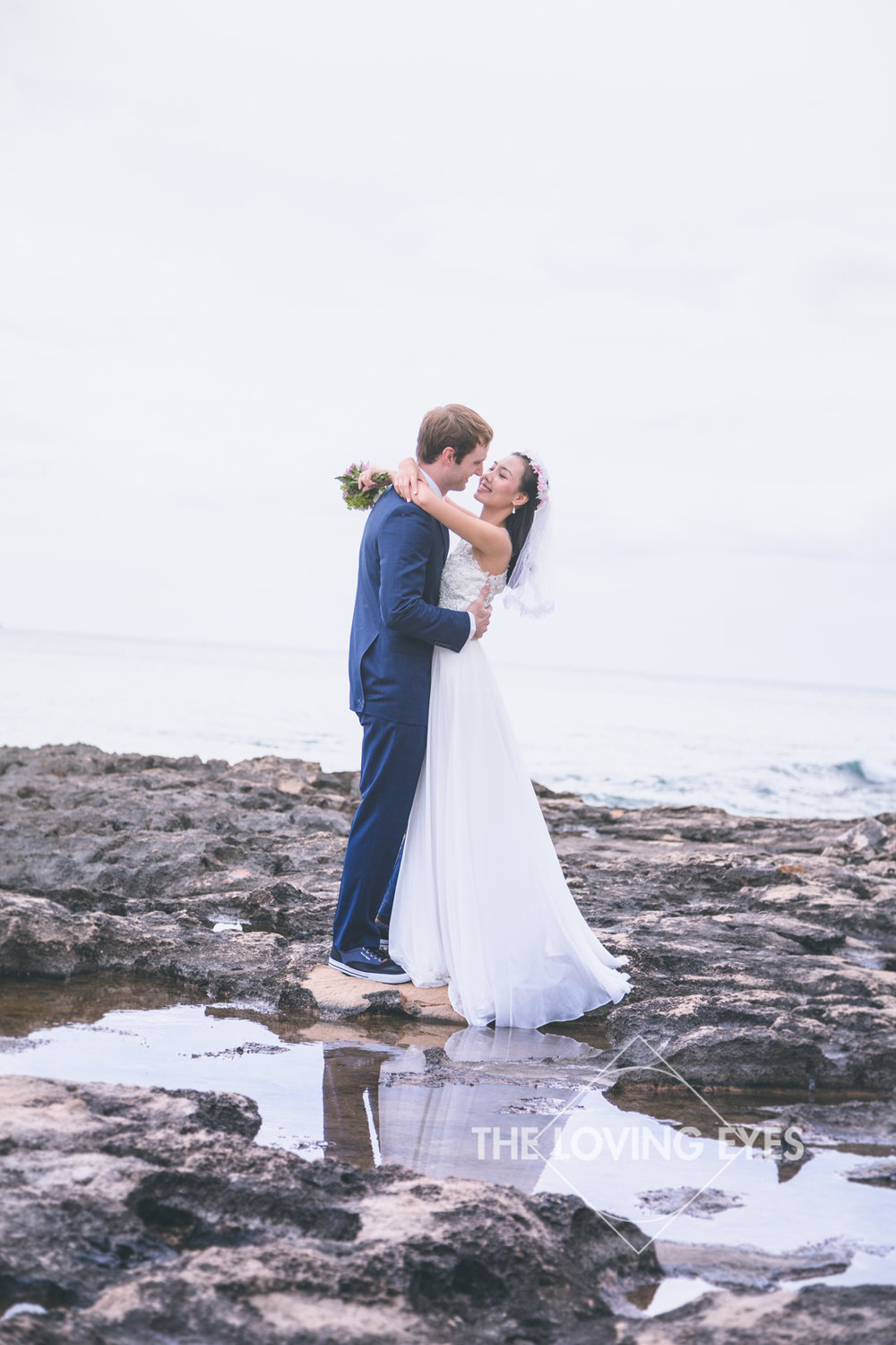 Bride and groom holding each other at the lagoon near the Four Seasons Resort at Ko Olina