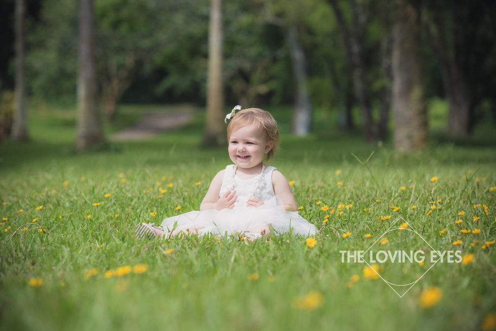 Toddler portrait sitting in flowers in Hawaii at Hoʻomaluhia Botanical Gardens