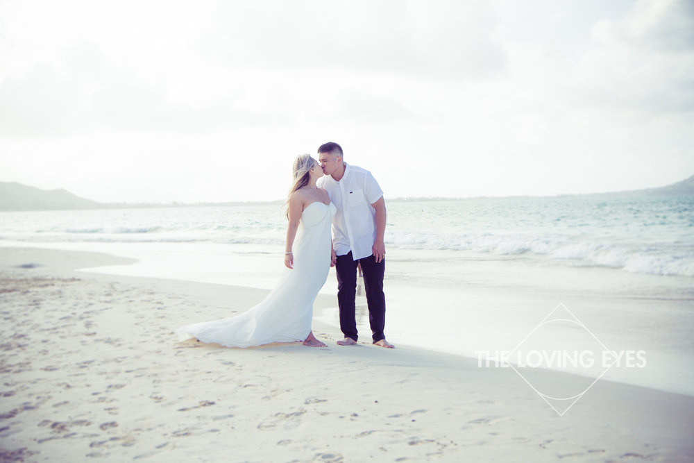 Couple walking and kissing on the beach during Hawaii engagement photography at Kailua Beach
