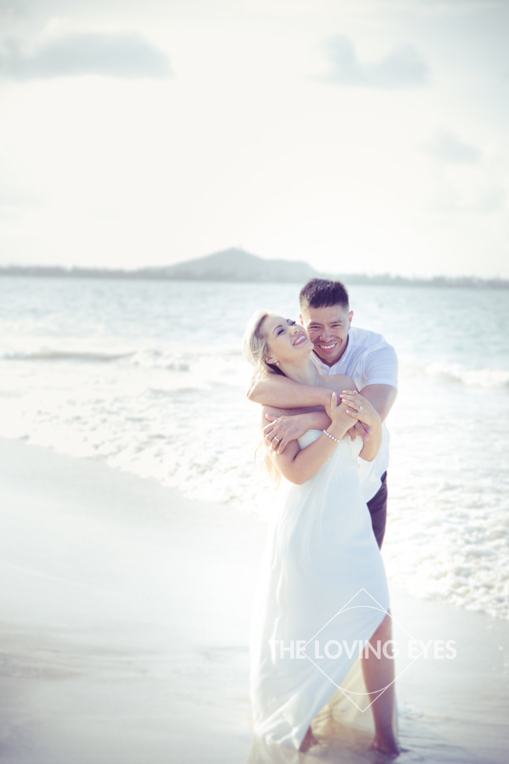 Couple hugging and playing on the beach during Hawaii engagement photography at Kailua Beach