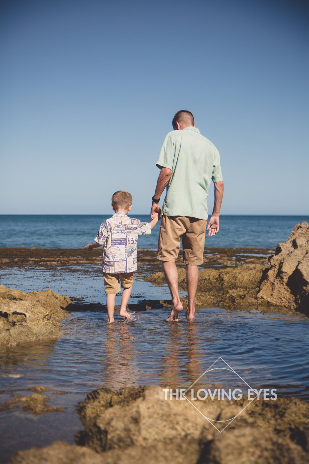 Father and son portrait walking hand in hand at tide pools at the beach in Ko Olina