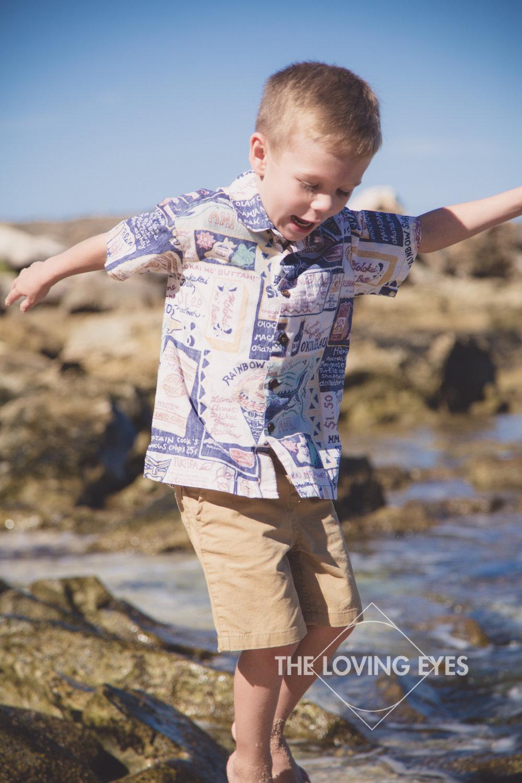 Happy boy jumping at the beach family portrait in Ko Olina