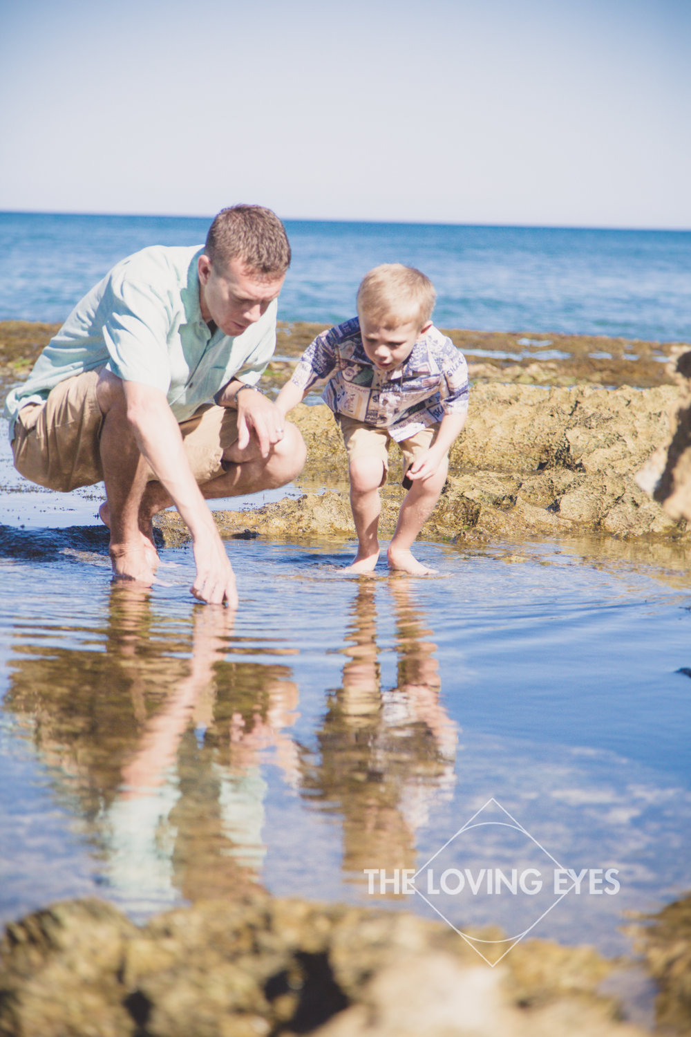Father and son portrait watching fish in tide pools at the beach in Ko Olina