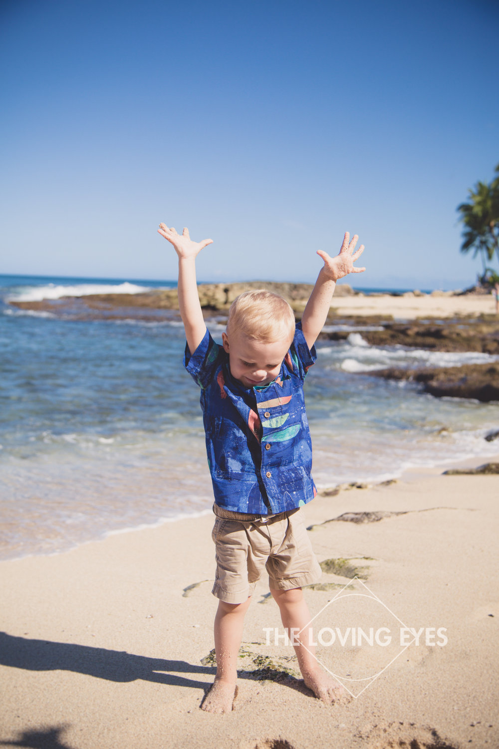 Happy toddler posing for family portrait at the beach in Ko Olina