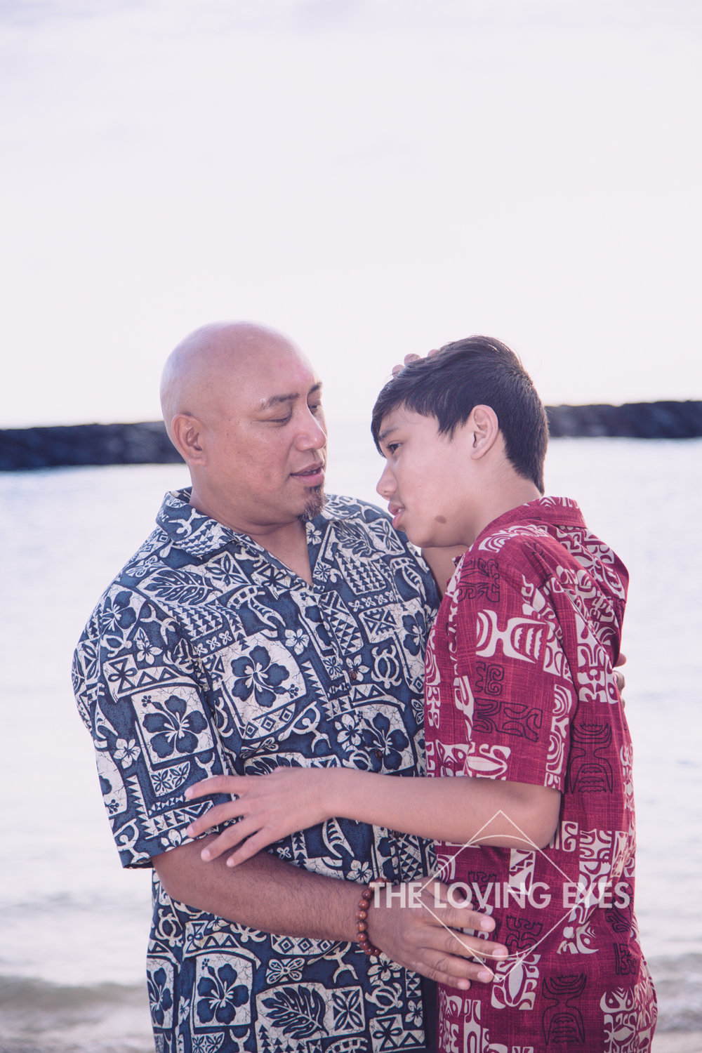 Father and son hugging on the beach at Ala Moana Beach Park in Hawaii