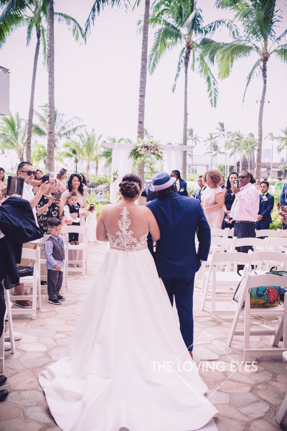 Bride escorted by father during wedding ceremony at Hilton Hawaiian Village Rainbow Suite in Waikiki