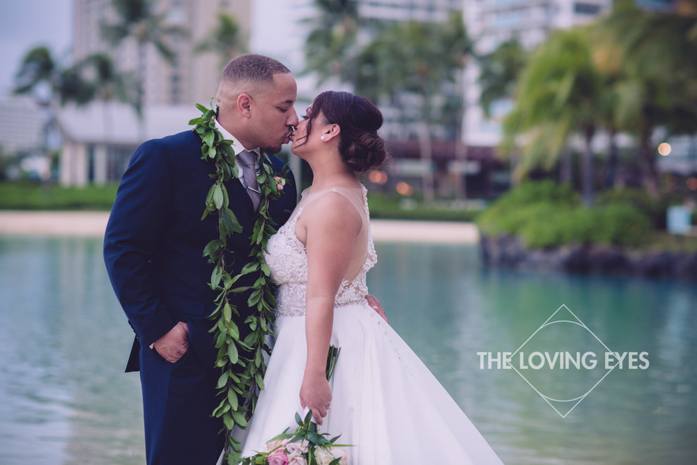 Bride and Groom kiss on the beach at Waikiki in Hawaii