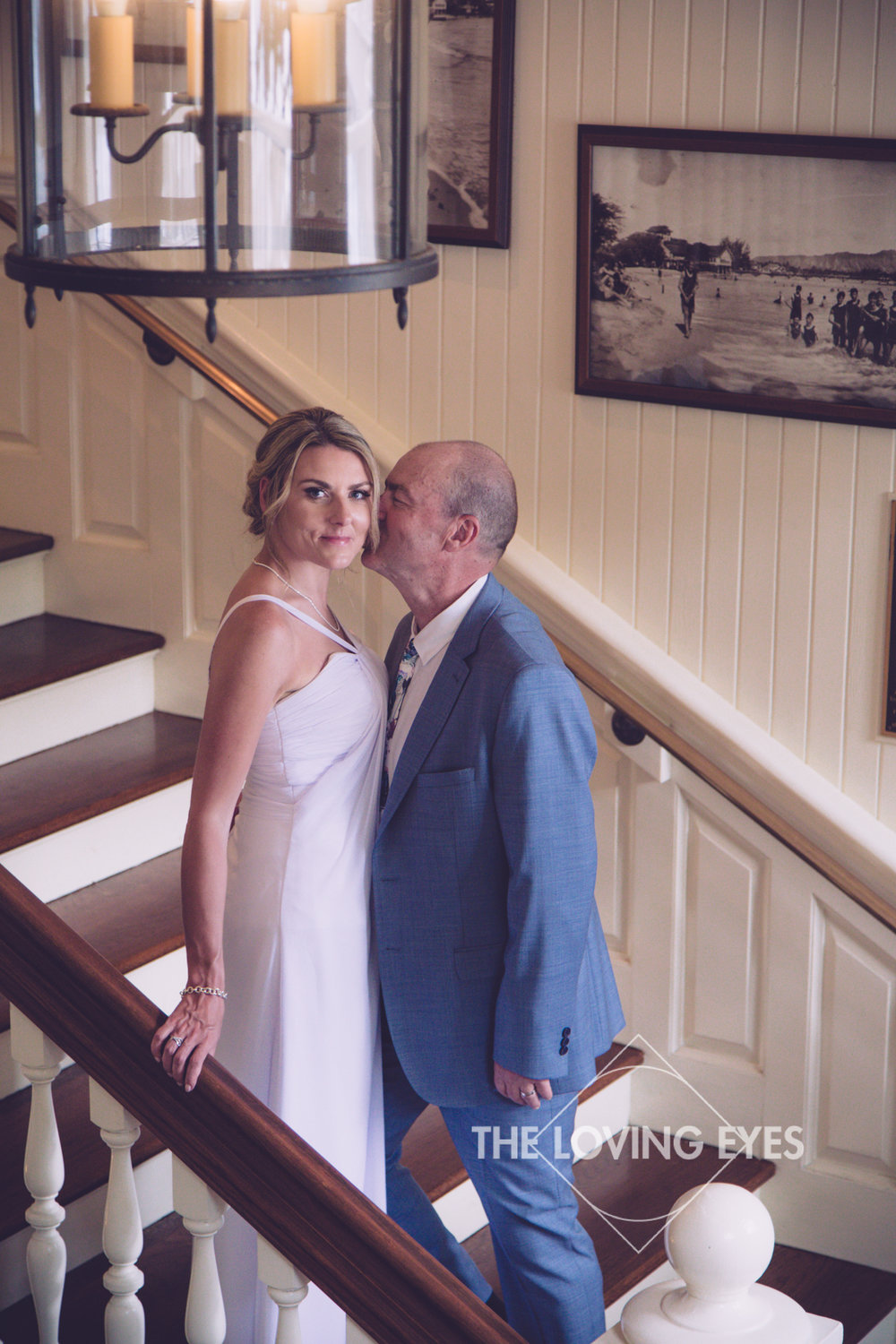 Bride and groom on their wedding day at the grand staircase of the Moana Surfrider in Waikiki