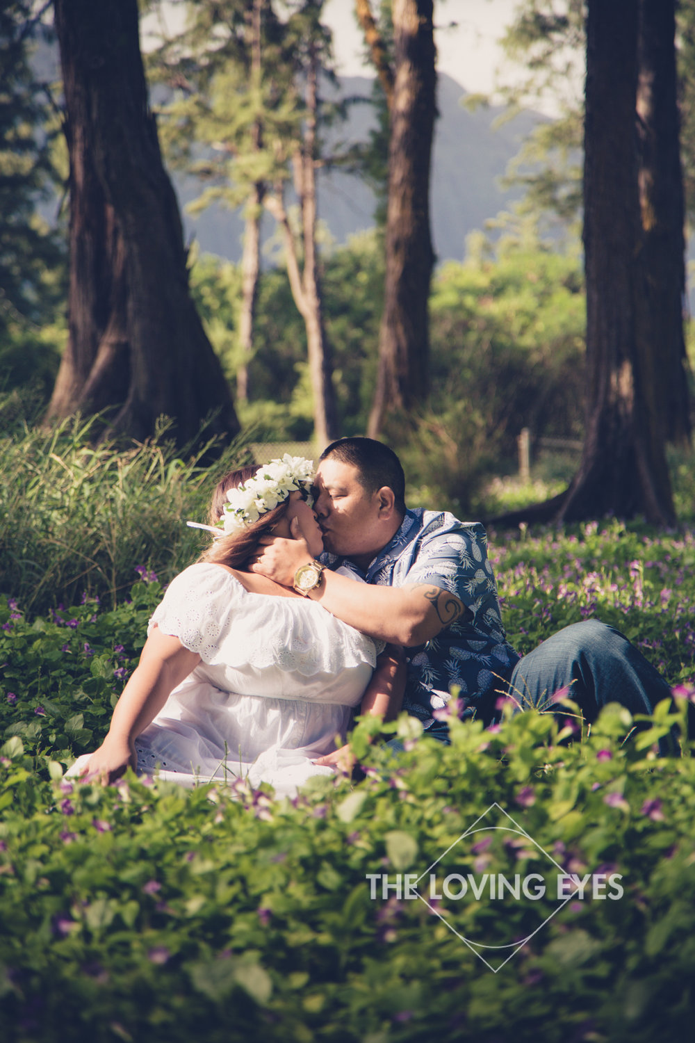 Romantic kiss engagement photo in a field of flowers in Waimanalo in Hawaii