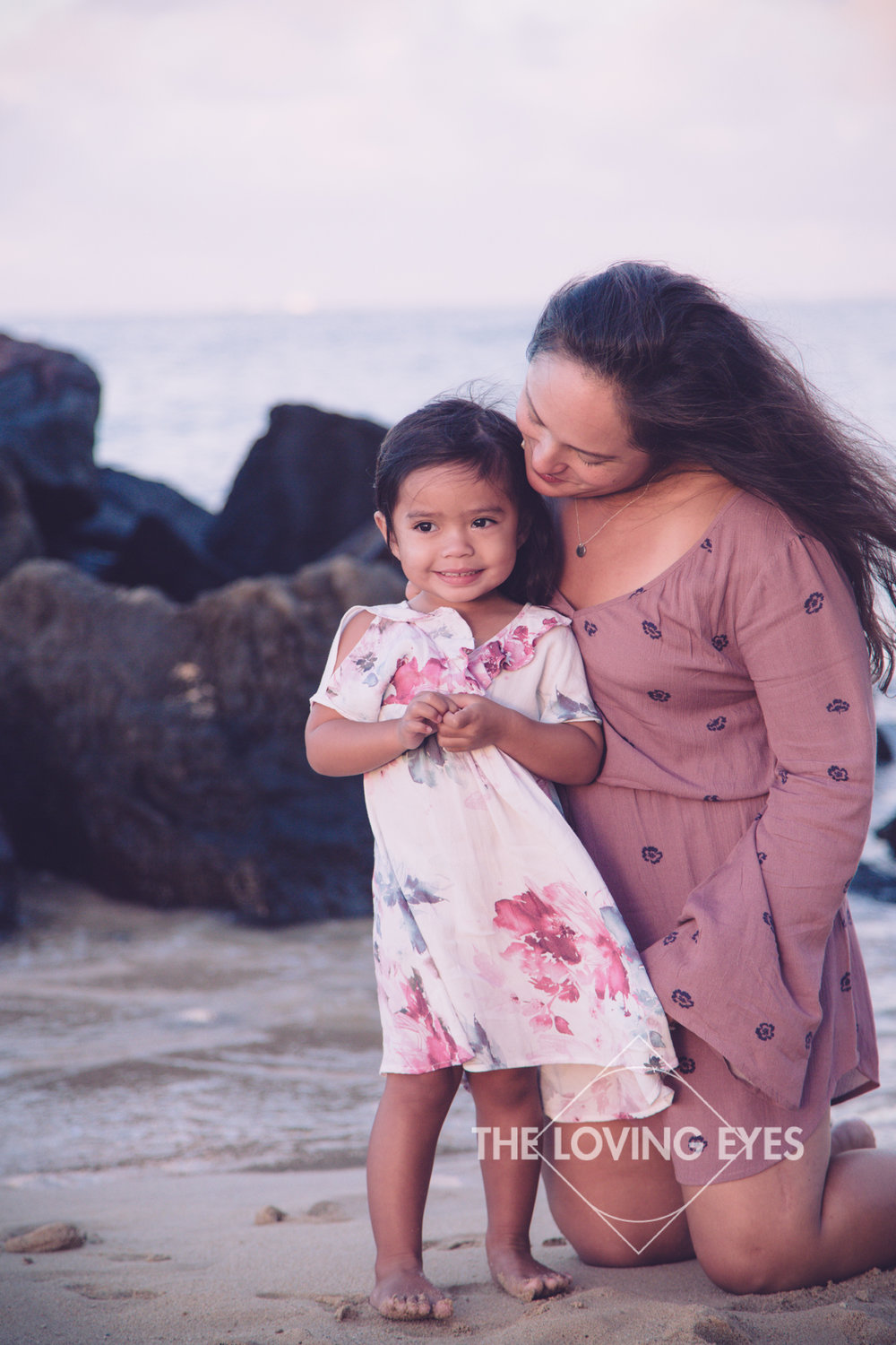 Mother and daughter on the beach in Waikiki during sunrise in Hawaii