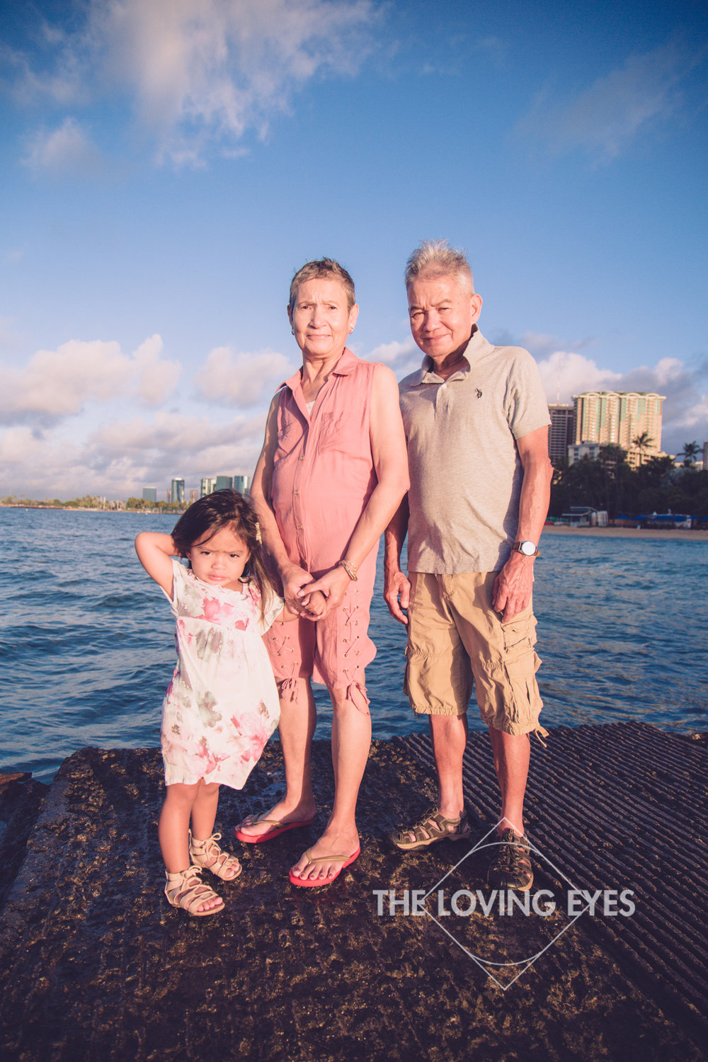Grandparents with their grand daughter on the beach in Waikiki in Hawaii