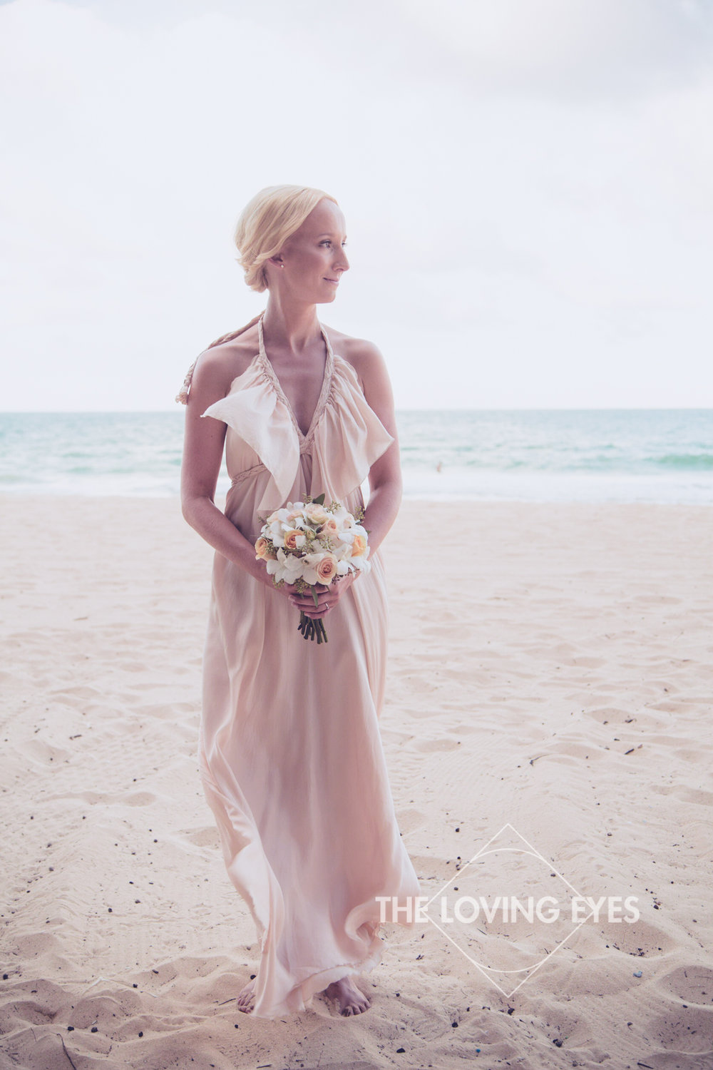 Bride with bouquet of flowers on the beach in Hawaii